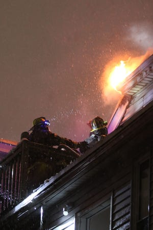 Firefighters work at a three-alarm fire at 69 West St. in Worcester as flames break through the corner of the building.