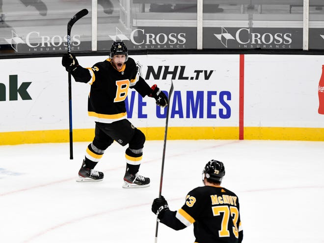 Bruins right wing Craig Smith, left, celebrates with defenseman Charlie McAvoy after scoring the winning goal in overtime Tuesday night against the Penguins at TD Garden.