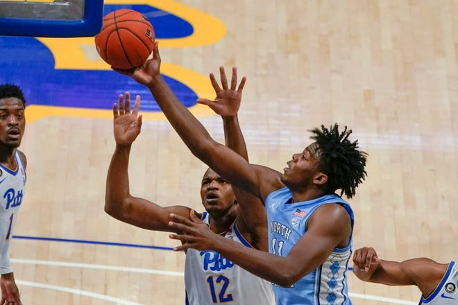 North Carolina's Day'Ron Sharpe, front, extends for a shot over Pittsburgh's Abdoul Karim Coulibaly during Tuesday night's game.