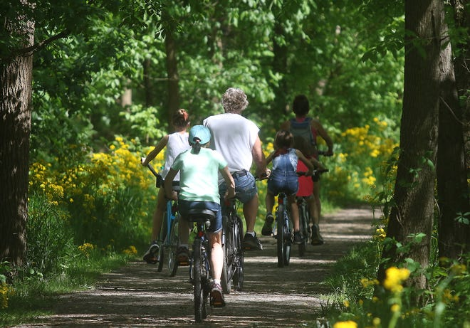 Biking/hiking trails are growing in popularity. In this Times-Reporter file photo, a family takes a bike ride on the Ohio and Erie Canal Towpath Trail near Zoar. New Philadelphia council authorized Mayor Joel Day to apply for funding to build trails in the city.