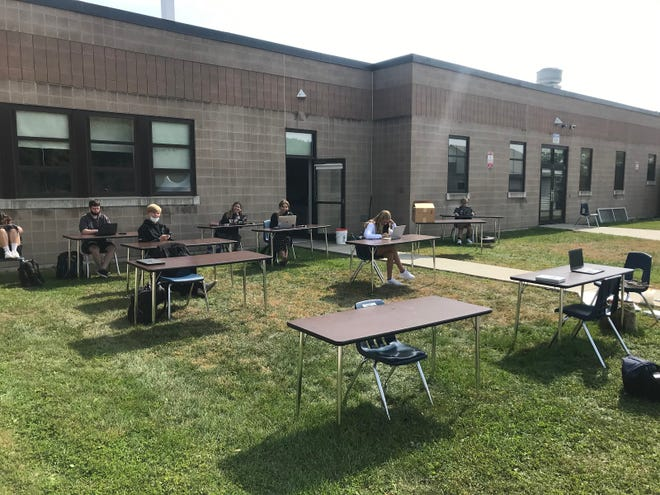 Champlain Valley Union High School students complete work at separate tables while limiting the spread of COVID-19 by being outside during the 2020-2021 school year. Being physically distant and masked for school learning twice a week has made it tougher for teens to maintain find ways to socialize.