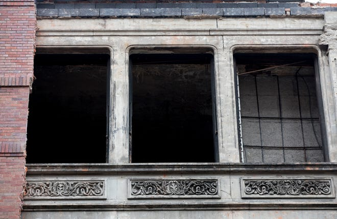 Crews removed some of the brick exterior of the building at 616 Race Street exposing the Victorian era storefront on Wednesday, Jan. 27, 2021, in Cincinnati. The Chong Inc., which was the most recent tenant, closed last March due to the new coronavirus pandemic.