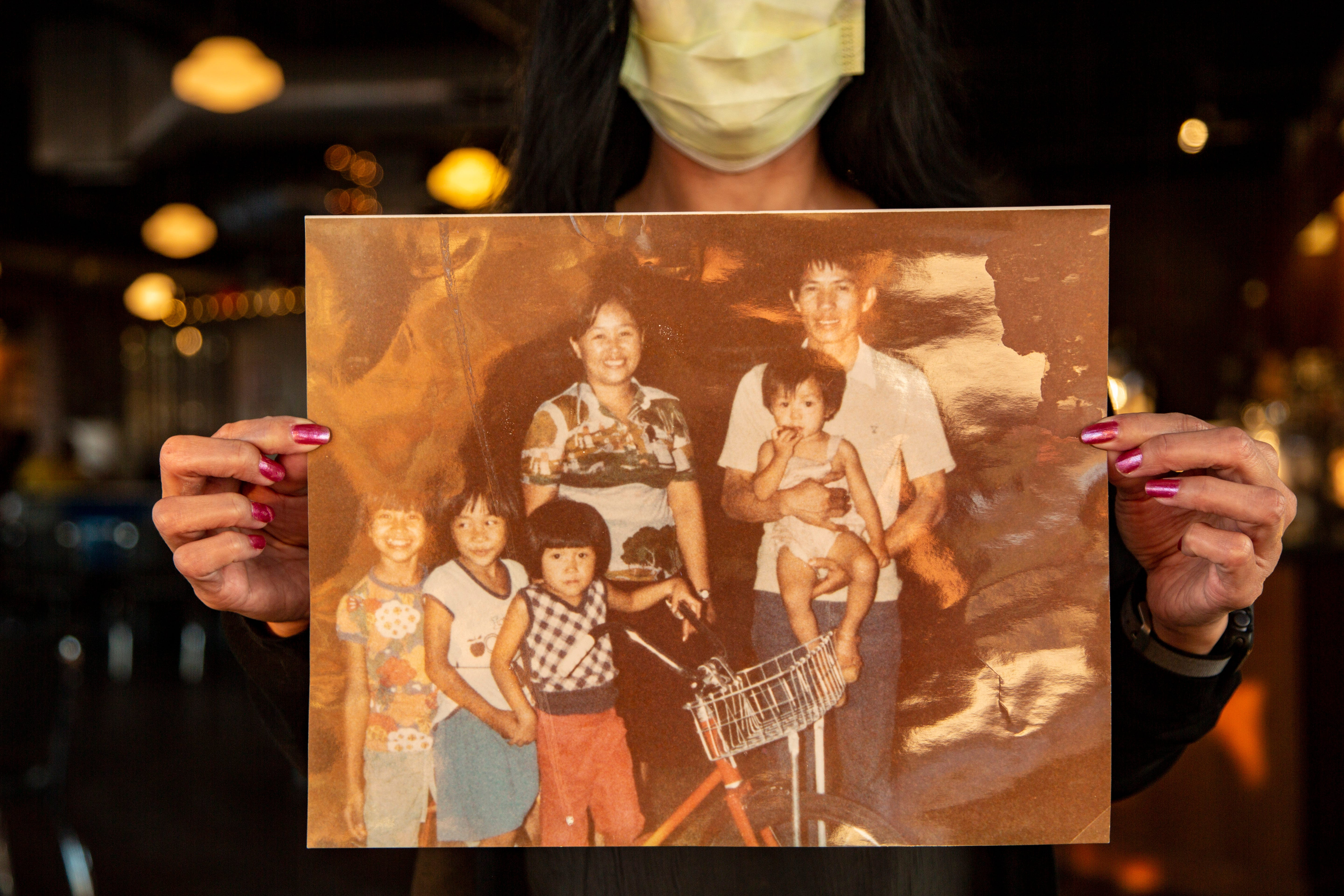 Jade Robinson holds a family photo taken in 1980 after her family immigrated to America from northern Thailand.