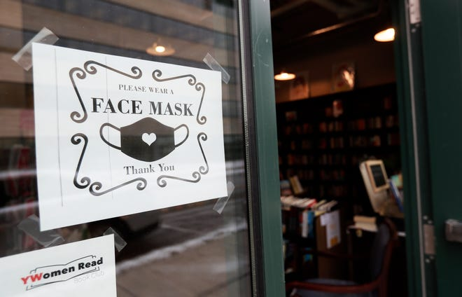 A sign in the window of Lion's Mouth Bookstore asks customers to wear a face mask inside the downtown Green Bay store.