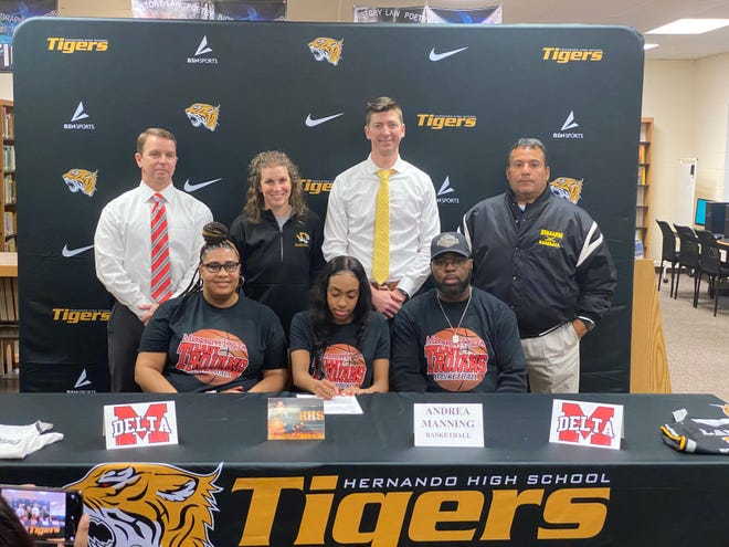 Hernando High School's Andrea Manning signed a scholarship to continue her basketball career at Mississippi Delta Community College on Wednesday, Jan. 27. Manning is joined by her parents; and (standing, from left) Hernando principal Duane Case, HHS assistant coach Jana Waller, HHS head coach Danny Forbes and HHS athletic director David Lara.