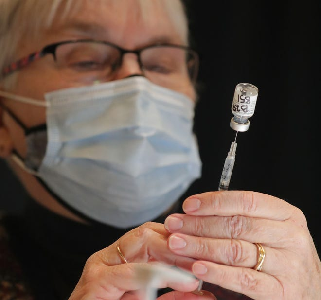Barbara Coyle, a temporary public health nurse with the City of Milwaukee, draws the COVID-19 vaccine into a syringe, making sure there are no bubbles, at the Wisconsin Center, 400 W. Wisconsin Ave.,  on Jan. 27, 2021.