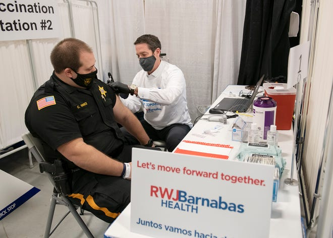 Dr. Christopher Freer, senior vice president for emergency and hospitalist medicine at RWJBarnabas Health, gives the first COVID-19 vaccination at the mega-site in Edison to Sheriff's Officer Christopher Vance.