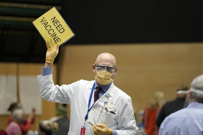 """In this Jan. 24, 2021, file photo, Dr. John Corman, the chief clinical officer for Virginia Mason Franciscan Health, holds a sign that reads """"Need Vaccine"""" to signal workers to bring him more doses of the Pfizer vaccine for COVID-19 as he works at a one-day vaccination clinic set up in an Amazon.com facility in Seattle. An increasing number of COVID-19 vaccination sites around the U.S. are canceling appointments because of vaccine shortages in a rollout so rife with confusion and unexplained bottlenecks. (AP Photo/Ted S. Warren, File)"""