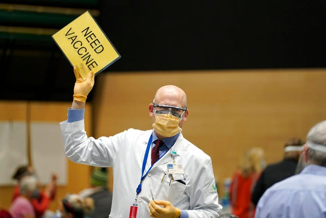 """FILE - In this Jan. 24, 2021, file photo, Dr. John Corman, the chief clinical officer for Virginia Mason Franciscan Health, holds a sign that reads """"Need Vaccine"""" to signal workers to bring him more doses of the Pfizer vaccine for COVID-19 as he works at a one-day vaccination clinic set up in an Amazon.com facility in Seattle. An increasing number of COVID-19 vaccination sites around the U.S. are canceling appointments because of vaccine shortages in a rollout so rife with confusion and unexplained bottlenecks. (AP Photo/Ted S. Warren, File)"""