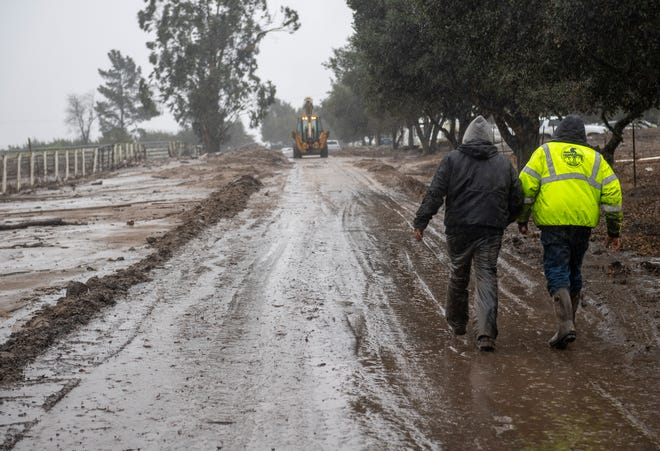 Residents living near a burn scar area from the River Fire evacuate dozens of horses on Wednesday, Jan. 27, 2021. Community members came together to help one another get through several inches of mud after a home near 844 River Road was damaged by a mudslide after last night's storm.