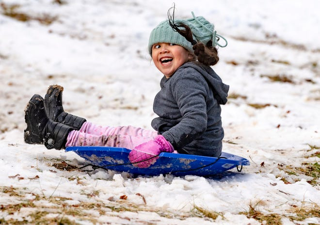 Angelita Meraz-Romero, 5, of Tulare giggles Tuesday, January 26, 2021 as she slides in a few inches of snow near Hospital Rock in Sequoia National Park. The snow was from the weekend storm. Several feet of snow are expected in the mountains before the end of the week.
