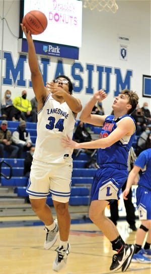 Zanesville's Xavier Riley lays the ball up against a Lakewood defender in Tuesday's 67-36 Licking County League win at Winland Memorial Gymnasium.