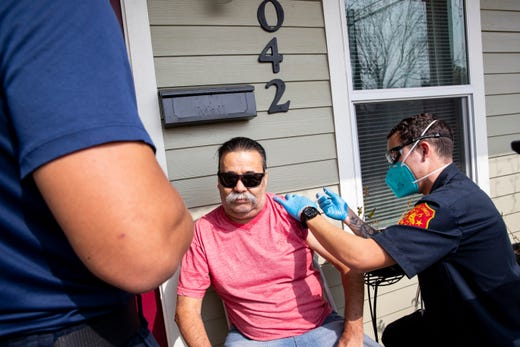 Corpus Christi firefighter cadet Marcus Maldonado gives Samuel Sanchez a COVID-19 vaccine outside this home during the first day of the Senior Vaccination Program in Corpus Christi, Texas on Jan. 26, 2021.  Fd Home Vaccinations 3