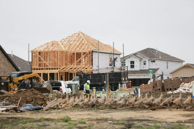Crews work on new homes in a Buda subdivision in this file photo.  Austin-area housing construction surged in 2020, as booming demand led to a record number of housing starts, according to industry data.