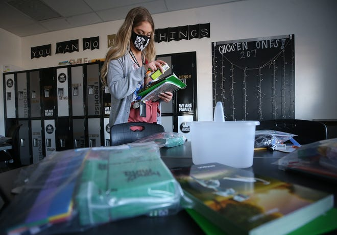 I Promise School teacher Kelley Pratt sorts through her students' work materials before dropping them off at their homes.
