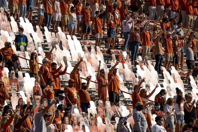 """Texas fans sing """"The Eyes of Texas"""" after the Longhorns' 17-13 win over West Virginia at Royal-Memorial Stadium in November. Due to COVID-19 restrictions, attendance at home games was capped well below the stadium's capacity."""