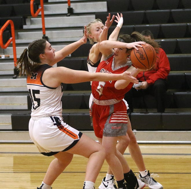 Marlington's Allison Lacher, left, and Mary Mason, back, box in Canton South's Abigail Hein during action at Marlington High School on Wednesday, January 27, 2021.