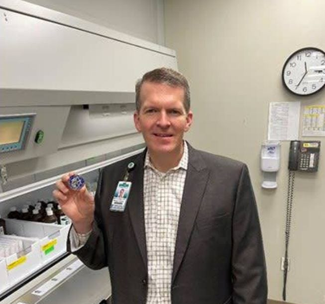Steven Howell, pharmacy manager at Integris Baptist Medical Center in Oklahoma City, with a challenge coin in recognition of his efforts to expand the supply of COVID-19 vaccine.