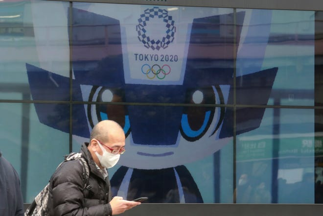 A man walks by an electric monitor promoting the Tokyo 2020 Olympics planned to start in the summer of 2021, in Tokyo, on Wednesday.