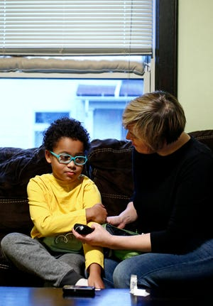 Mandy Seaton holds an insulin pump for her son, Ronin, 9, at their North Side home Wednesday. Both live with Type 1 diabetes, which means they would die without insulin. She considers herself lucky because her husband's job with Franklin County includes good insurance that covers all but about $3,000 of the annual cost of the medicine, which has skyrocketed in recent years.