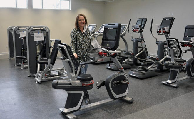Gwen Sommer, CEO of the YMCA of Wayne County, stands with new machines purchased by West View Healthy Living with a grant from the Wayne County Community Foundation at West View's new fitness center.