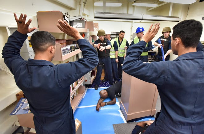 Petty Officer 2nd Class Jose Gordillo Gomez (left) and Petty Officer 3rd Class Nicholas Tutt hold their hands up as they play the part of hostages during an active shooter drill aboard the USS Paul Ignatius as part of 2020's Exercise Solid Curtain/Citadel Shield at Naval Station Mayport.
