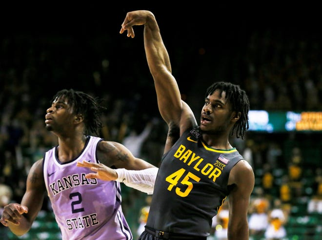 Baylor Bears Davion Mitchell (45) follows through on a 3-point shot over Kansas State's Selton Miguel (2) during the second half Wednesday at Ferrell Center in Waco, Texas. Mitchell made seven 3-pointers and finished with a career-high 31 points.