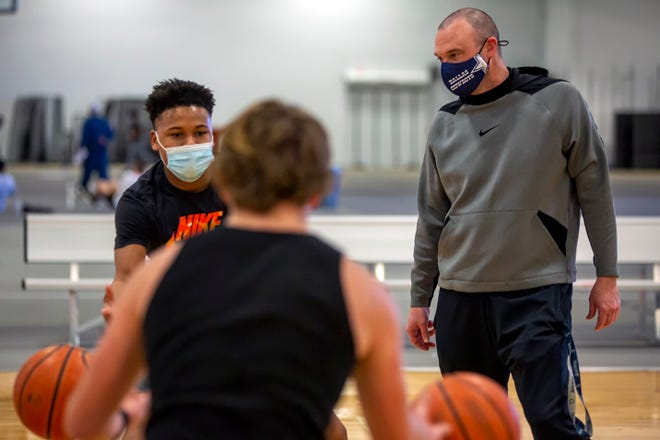 Galesburg head boys basketball coach Ryan Hart, right, watches over a drill during practice for the Silver Streaks in the GHS Fieldhouse on Thursday, Jan. 28, 2021.
