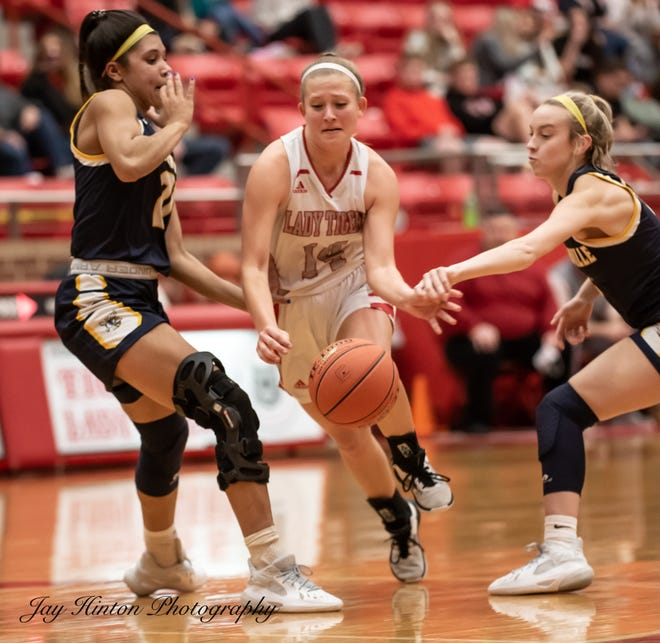 Glen Rose's Hannah Cantwell, who led the Lady Tigers with 16 points, splits a pair of Honeybee defenders while driving to the basket.