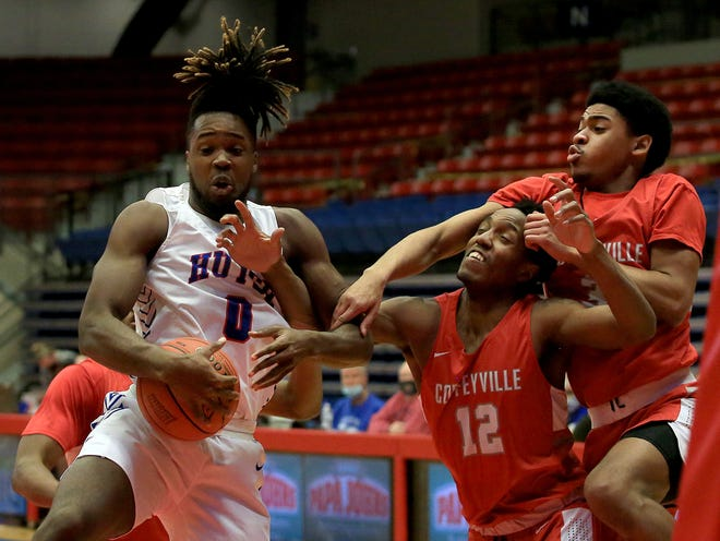 Hutchinson Community College's Bryant Selebangue (0) grabs the rebound against Coffeyville's Noah Butler (12) and Bostyn Holt (03) during their game at the Sports Arena. Coffeyville defeated HCC 88-68. HCC will be allowing some fans into home games at the arena starting Saturday.