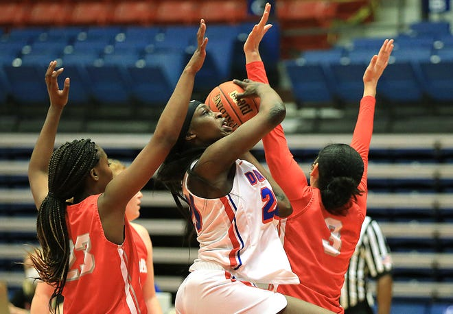 Hutchinson Community College's Lojong Gore (20) drives to the basket against Coffeyville's Nakia Cullom (23) and Amiya Josey (03) during their game Wednesday evening at the Sports Arena. HCC defeated Coffeyville 70-63.