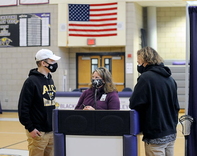 Blackstone Valley Tech Regional High School Athletic Director Michele Denise speaks with Ben Hardcastle, left, and Jack Kinsella, before their National Letter of Intent Signing ceremony, Jan. 28, 2021.