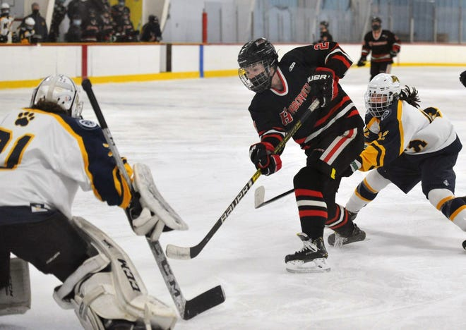 Hingham's Ryan Maguire, center, takes a shot on Notre Dame Academy goalie Lily Prendergast as Notre Dame Academy's Jules Connors, right, defends during girls hockey at Pilgrim Arena in Hingham, Wednesday, Jan. 27, 2021.