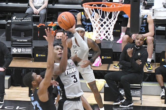 Providence's David Duke goes strong to the hoop against Marquette's Jamal Cain on Wednesday night at Alumni Hall. Duke finished with 31 points in the Friars' overtime victory.