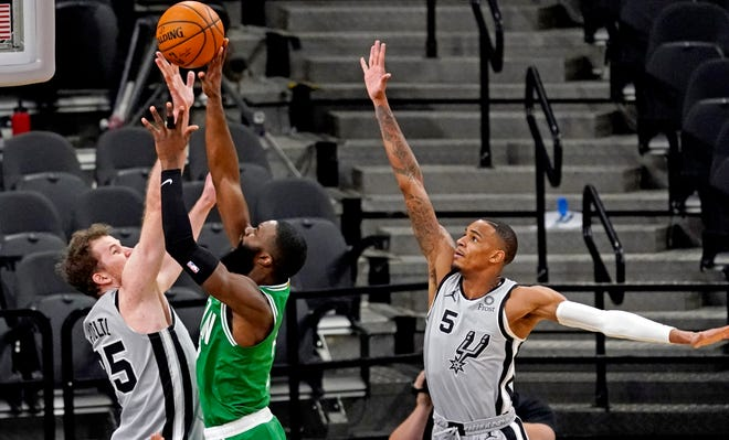 Celtics guard Jaylen Brown, center, shoots against Spurs guard Dejounte Murray during the fourth quarter on Wednesday night in San Antonio.