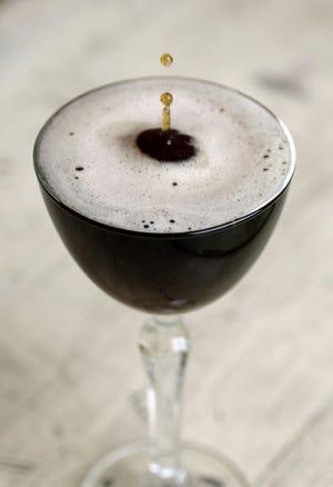 Espresso Martini made with Rhodium Coffee &  Black Walnut Vodka drips into a glass.