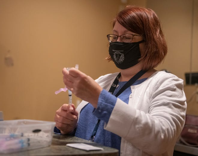 Marianne Kitakis, Portage County Health Department nurse, prepares doses of the COVID-19 dose during a recent health department clinic.
