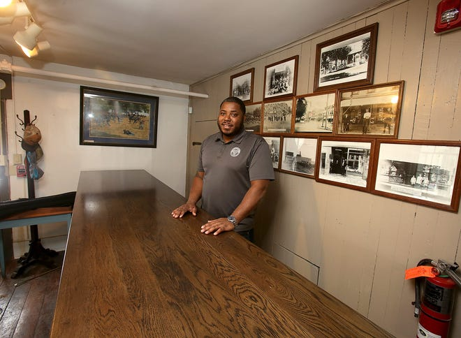 Demond Germany , owner of Scratch Steakhouse stands behind the bar with historic  photos of Carrolton at his new Carrolton location.