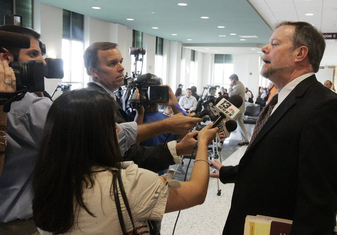 David Doll, pictured in 2009 taking questions from reporters about his client Katie Stockton's murder trial, will retire April 23 after serving four years as Winnebago County public defender.