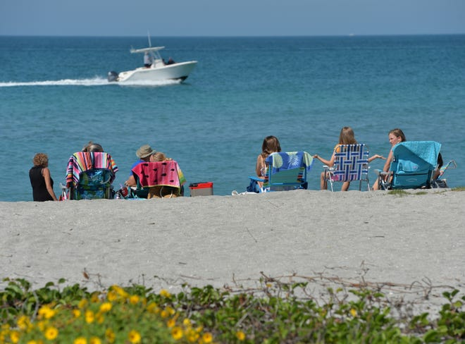People enjoy a day at Turtle Beach on March 18, 2020, at the beginning of the coronavirus pandemic. Economist Dr. Hank Fishkind said tourism will recover once COVID-19 vaccines are more widely distributed.