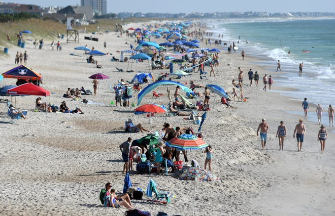 Crowds can be seen looking north from Johnnie Mercer's Fishing Pier at the beginning of Labor Day weekend in 2020 in Wrightsville Beach, N.C.