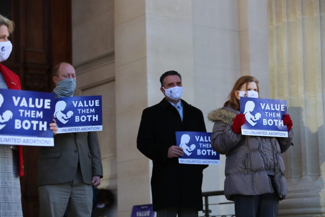 Senate President Ty Masterson, second from right, holds a sign supporting the Value Them Both amendment.
