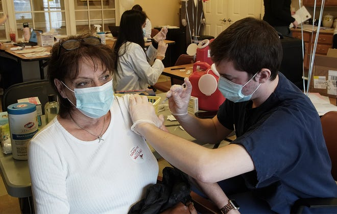 All American Assisted Living in Raynham receptionist Christine Eisner gets her COVID-19 vaccination from pharmacist student Will Cardingley in this January file photo.
