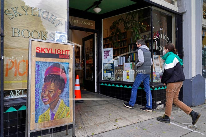 Eric and Tess from Pasadena, Calif., enter the Skylight Book store, decorated with a poster of American poet Amanda Gorman, in Los Feliz neighborhood of Los Angeles Monday, Jan. 25, 2021.