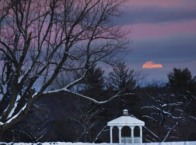 """BARRE - A """"Full Wolf Moon"""" is just visible through clouds above a gazebo at Harty Farm on Thursday."""