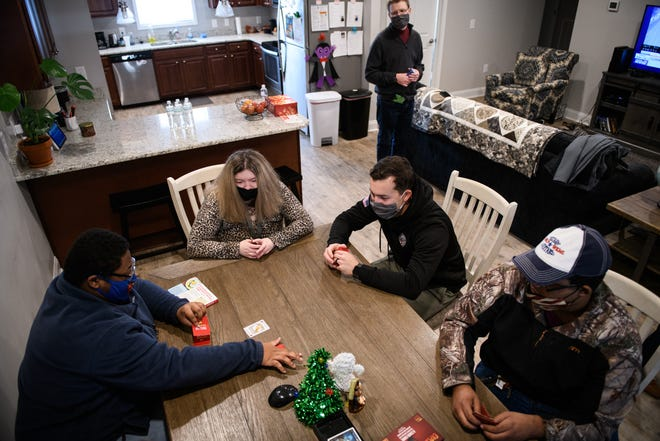 Fayetteville Friendship House residents hang out in one of the apartments and play a card game Thursday.
