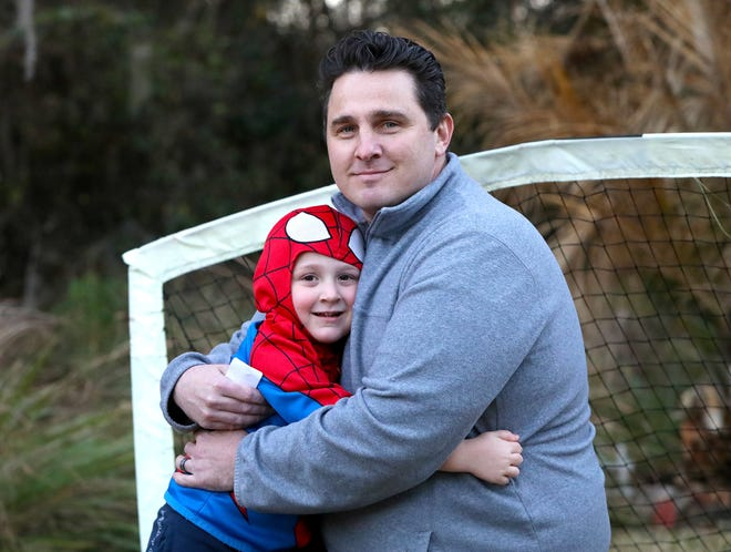 """Steven Kay and his 5-year-old son Parker pose for a photo Thursday at their home in Gainesville. Parker's mother, Kristin, 31, has been hospitalized for a month with COVID-19. """"I'm really scared,"""" Steven Kay said about his wife, """"but I'm hopeful. It's a wave of emotion."""""""