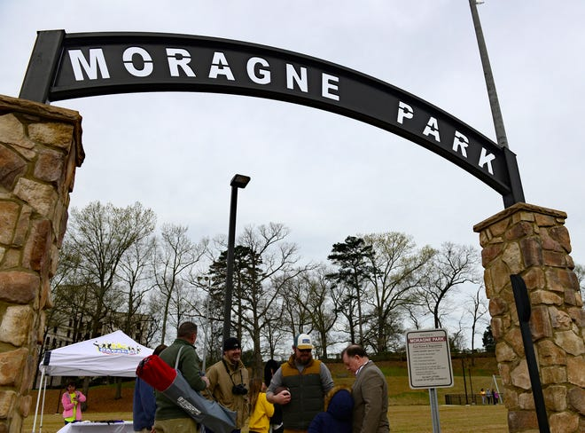 Visitors to the opening ceremony for the newly renovated Moragne Park stand near the main entrance on Saturday, March 16, 2019.