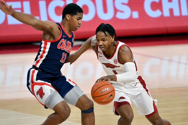 Arkansas guard JD Notae (1) tries to get past Mississippi defender Matthew Murrell (11) during the first half of an NCAA college basketball game Wednesday, Jan. 27, 2021, in Fayetteville. (AP Photo/Michael Woods)