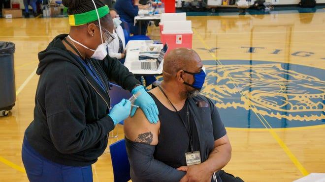 John P. Parker Elementary School building engineer Lanier Hardy receives the COVID-19 vaccine.